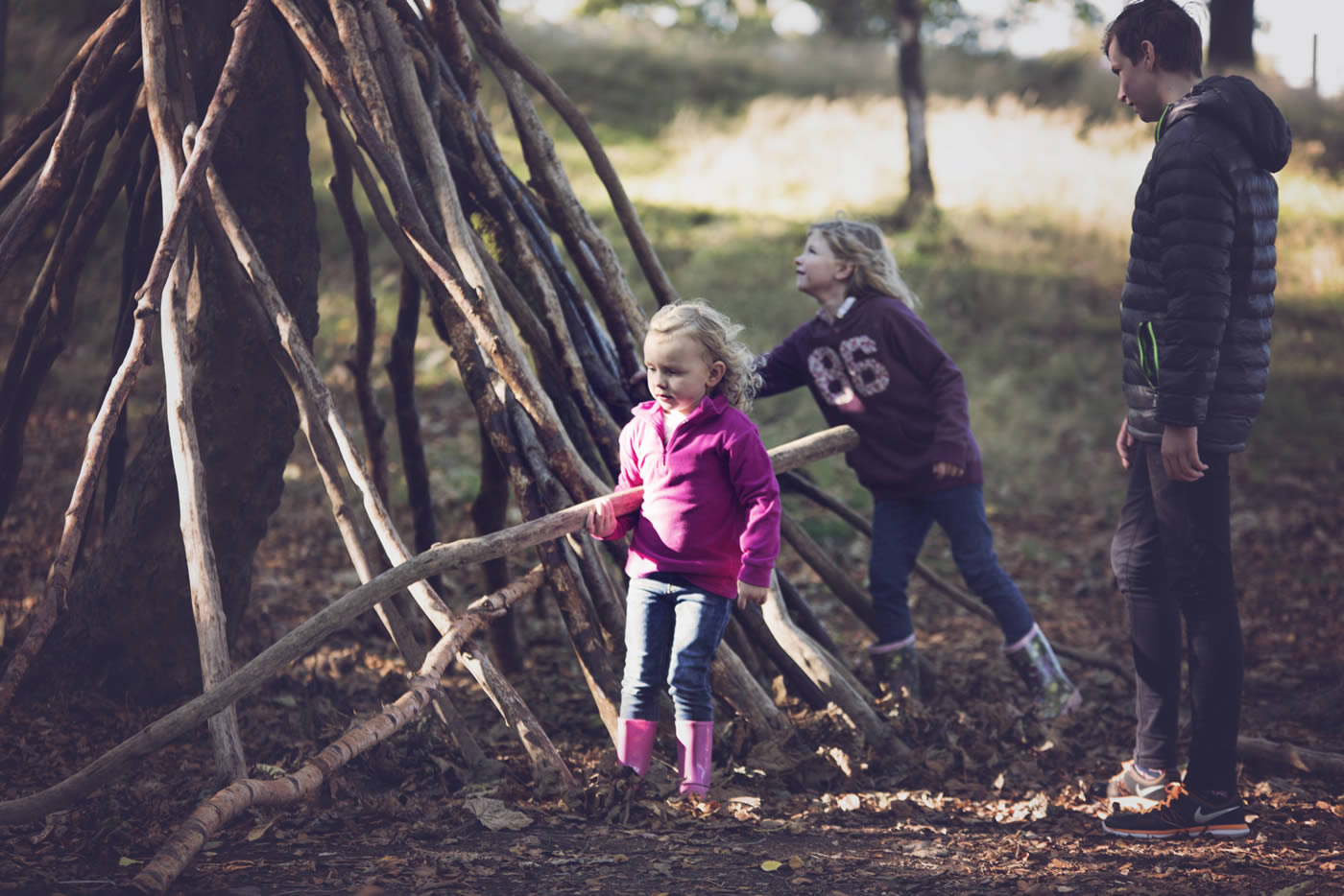 Two children building dens in the forest