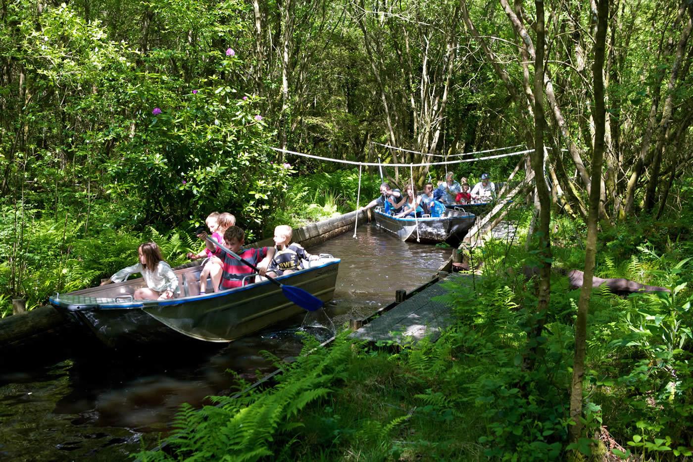 Children on boat ride through forest